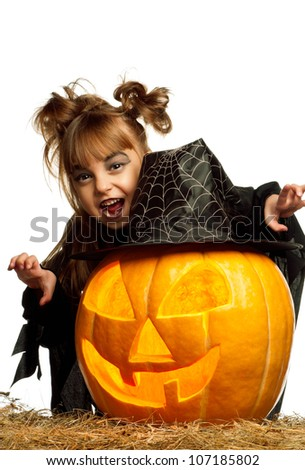 Portrait of little girl in black clothing with pumpkin on white background - stock photo