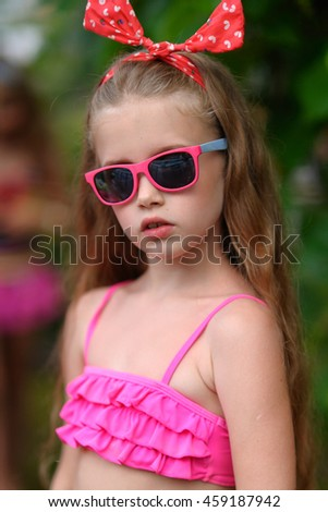 portrait of little girl in tropical style in a swimming pool - stock photo