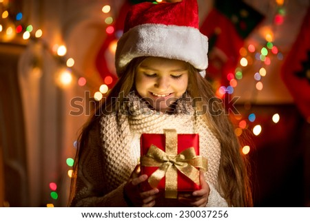 Portrait of little girl looking at open box with Christmas present - stock photo