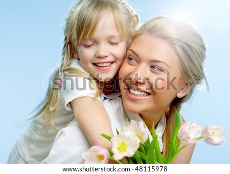 Portrait of little girl loving mother holding her and tulips - stock photo