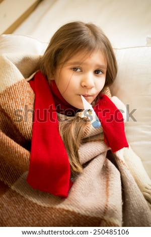 Portrait of little girl lying in bed and holding thermometer in mouth - stock photo