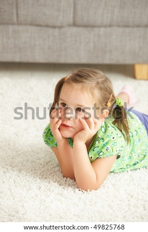 Portrait of little girl lying on floor at home looking away. - stock photo