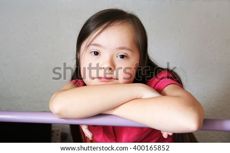 Portrait of little girl on the backgroung of the grey wall - stock photo