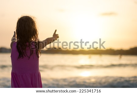 Portrait of little girl on the beach. Back view. - stock photo