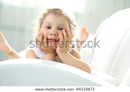 Portrait of little girl on white sofa at home - stock photo