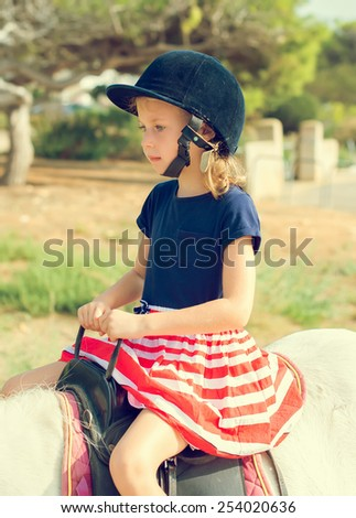 Portrait of little girl riding pony.  - stock photo