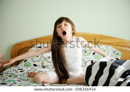 Portrait of little girl sitting in bed in early morning - stock photo