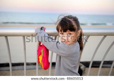 Portrait of little girl standing near fence on ocean shore promenade - stock photo