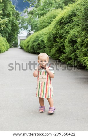 Portrait of little girl walking along the alley of the park with sunglasses in his hand - stock photo