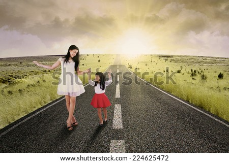 Portrait of little girl walking on the road while holding hands with her mother - stock photo