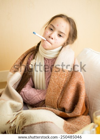 Portrait of little girl with chickenpox holding thermometer in mouth - stock photo