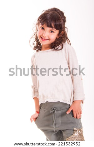 portrait of little girl with hands in pockets on white background   - stock photo