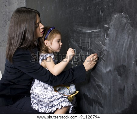 portrait of little girl with mother at blackboard, making lessons - stock photo