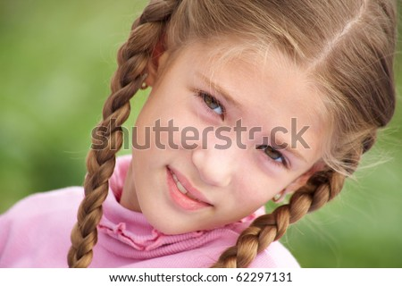 portrait of little girl with pigtails smiling at the camera against background of green