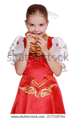 Portrait of little girl with round cracknel isolated over white background on Holiday theme/Nice young girl with lovely smile wearing traditional russian costume