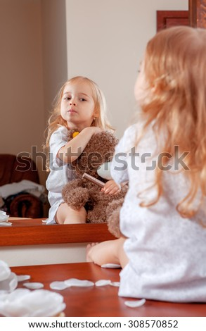 Portrait of little girl with teddy bear looking through near mirror - stock photo