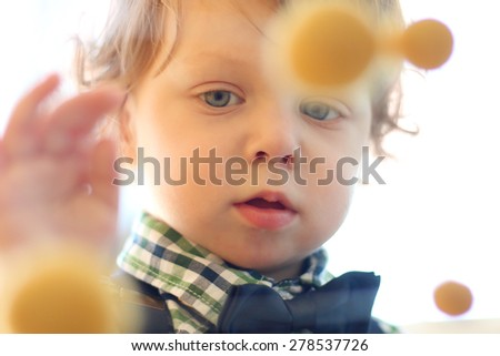 Portrait of little handsome boy with curly hair touching yellow balls. Close up view - stock photo