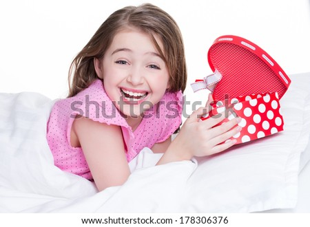 Portrait of little happy girl with a gift lying on the bed - isolated on white. - stock photo