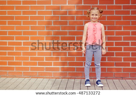 Portrait of little kid girl  laughing at a blank empty bricks wall background