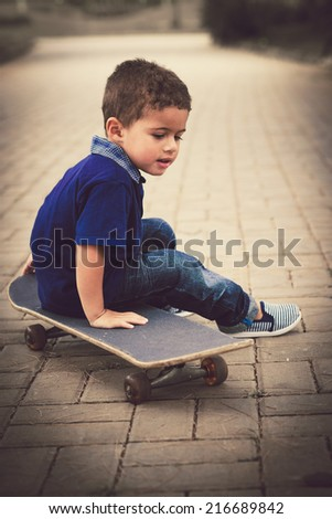 Portrait of little kid sitting on the skateboard