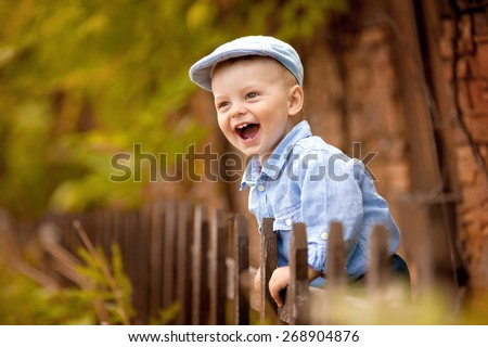 portrait of little laughing boy in the blue shirt and  cap is standing near the wooden fence in the nature - stock photo