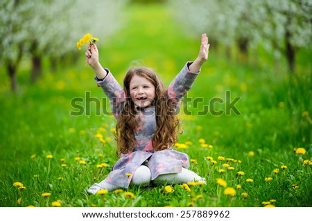 Portrait of Little pretty girl in the green blooming garden  - stock photo