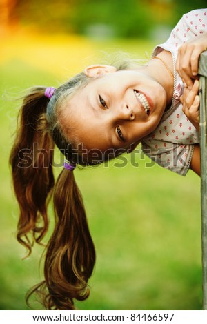 Portrait of little pretty laughing girl playing at summer green park. - stock photo