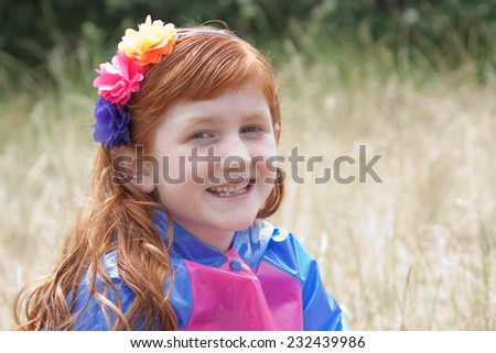 portrait of little red haired girl in brightly coloured plastic jacket and flowery headband  - stock photo