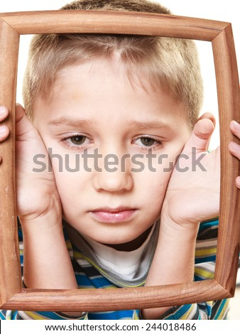Portrait of little sad blonde boy child holding photo frame framing his face looking up studio shot isolated on white