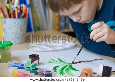 Portrait of little school boy sitting at the table and drawing palm tree. After school activities at home. Education. Small boy creating handmade cards. - stock photo