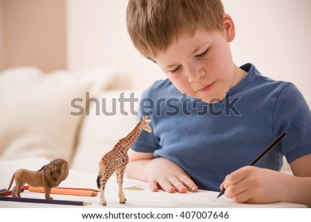 Portrait of little school boy sitting at the table and drawing with color paint. After school activities at home. Education. Small boy creating handmade cards.