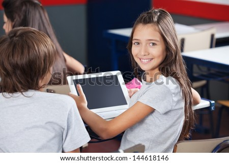 Portrait of little schoolgirl holding digital tablet at desk with classmates in classroom - stock photo