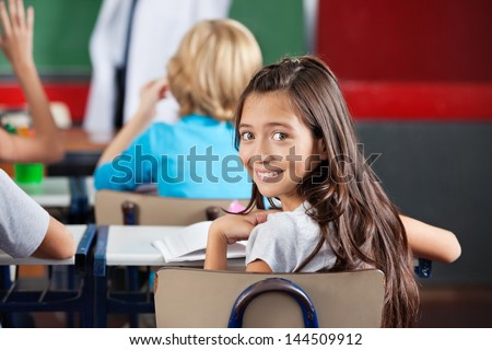 Portrait of little schoolgirl sitting at desk with classmates in classroom