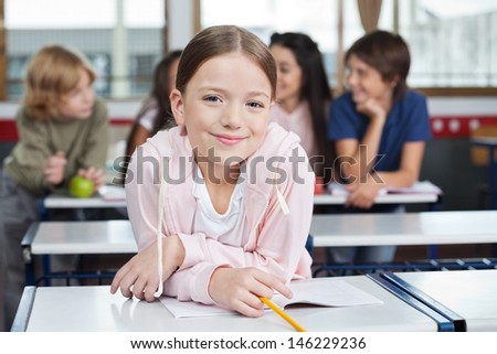 Portrait of little schoolgirl smiling while leaning on desk with classmates in background - stock photo