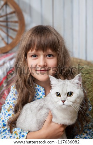 Portrait of little sincere friendly blond girl villager sitting with white cat in hands in wooden barn - stock photo