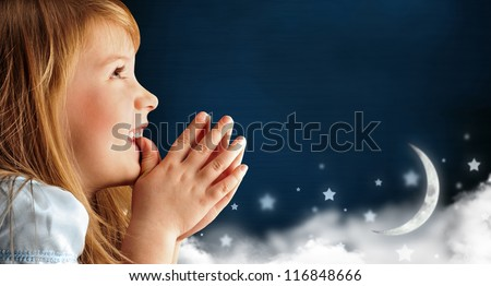 Portrait of little smiling praying girl in blue dress against dark fairy sky background with moon and stars. Lots of copyspace - stock photo