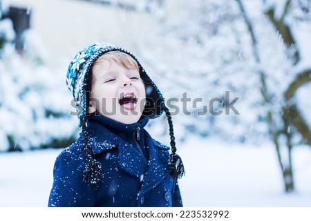 Portrait of Little toddler boy in winter clothes with falling snow - stock photo