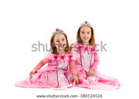 Portrait of Little Twin Girls dressed as princess in pink. Happy children ready for costume party. Cute smiling joyful twins are wearing royalty costume of princess or queen. - stock photo