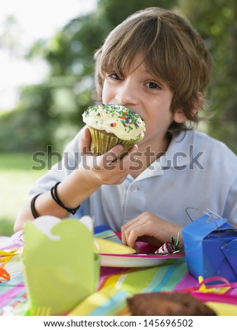 Portrait of little young boy eating cupcake at the outdoor birthday party - stock photo