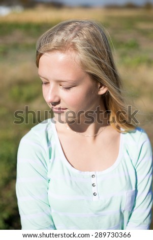Portrait of lonely blond teenage girl wearing white blouse daydreaming on rural background copyspace portrait - stock photo