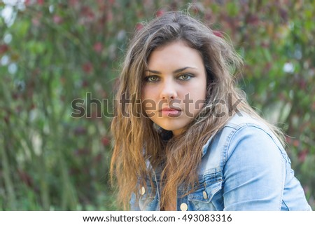 Portrait of long hair brunette teenage girl outdoors. Girl is looking at the camera.