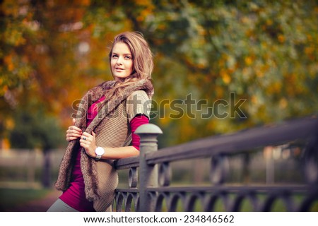 Portrait of long-haired beautiful girl in a knitted jacket in autumn - stock photo