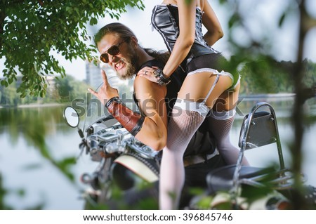 Portrait of long-haired biker guy and girl in sexy lingerie on the motorcycle. Rear view. Man wearing sunglasses and giving the devil horns gesture. Woman bottom, close up. Tilt lens blur effect - stock photo