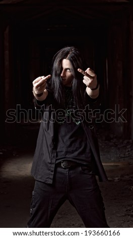 Portrait of long-haired young man making offensive gesture (middle fingers) - stock photo