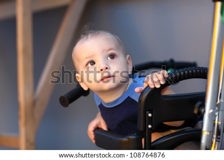 Portrait of looking child on a tricycle