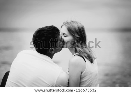 Portrait of love couple kissing outdoor in park looking happy - stock photo