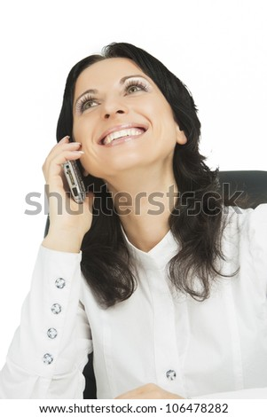 portrait of lovely brunette businesswoman sitting and smiling on chair while talking on mobile phone and discussing isolated over white - stock photo