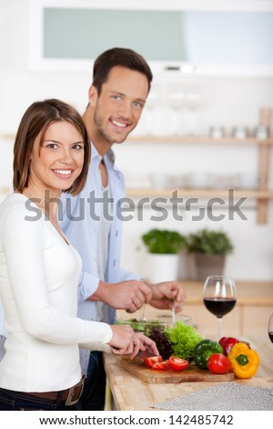 Portrait of lovely couple cooking in their kitchen - stock photo