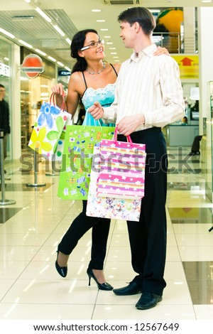 Portrait of lovely couple standing with shopping bags in the department store - stock photo
