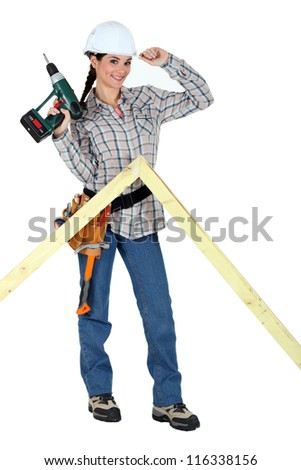 portrait of lovely female carpenter holding electric drill
